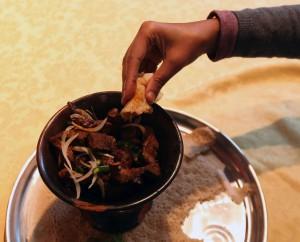 Fingertechnik. Gegessen wird mit der rechten Hand. Dabei ersetzt das Injera sowohl den Teller als auch das Besteck. Man reißt kleine Teile des Fladens ab und ergreift damit ein Stück der Fleisch- oder Gemüsebeilage und führt es zum Mund. Bis zu 5 Gästen essen aus einer Platte. Es gilt als besonders freundschaftlich, den Menschen, mit denen das Mahl geteilt wird, hin und wieder eine Portion direkt in den Mund zu stecken. Diese bezeichnet man Gursha.